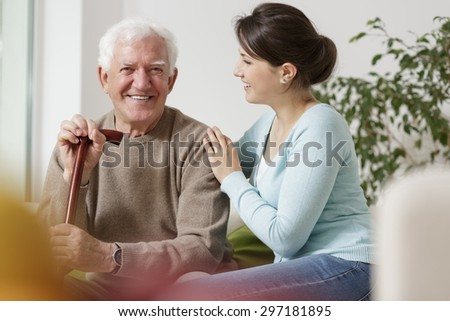 Beauty granddaughter caring about her disabled grandfather - stock photo