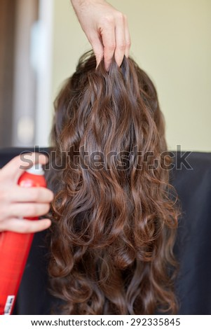 beauty, hairstyle and people concept - closeup of woman head and stylist hands with hair spray making hairdo at salon - stock photo