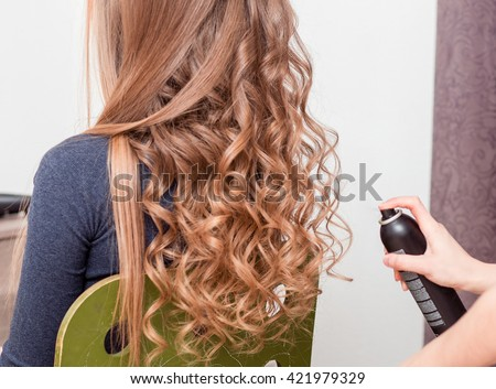 beauty, hairstyle and people concept - closeup of woman head and stylist hands with hair spray making hairdo at salon barber - stock photo