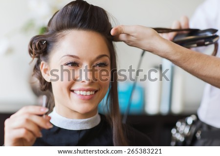 beauty, hairstyle and people concept - happy young woman and hairdresser with hair iron making hairdo at hair salon - stock photo