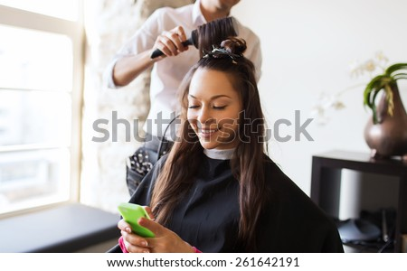 beauty, hairstyle and people concept - happy young woman with smartphone and hairdresser making hair styling at salon - stock photo