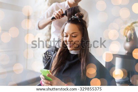beauty, hairstyle and people concept - happy young woman with smartphone and hairdresser making hair styling at salon over holidays lights - stock photo