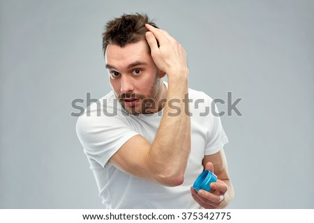 beauty, hairstyle, haircare and people concept - happy young man styling his hair with wax or gel over gray background - stock photo