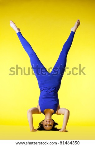 Beauty happy yoga master stand on head - stock photo