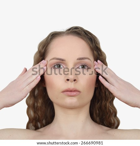 Beauty, health, make up and skin care concept - Young woman makes facial massage on light gray background - stock photo