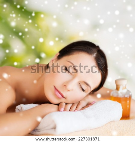 beauty, health, people and spa concept - beautiful young woman with body oil in spa over green background