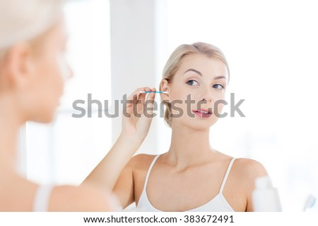 beauty, hygiene and people concept - young woman cleaning ear with cotton swab and looking to mirror at home bathroom - stock photo