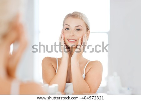 beauty, hygiene, morning and people concept - smiling young woman looking to mirror at home bathroom - stock photo
