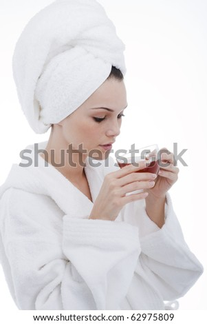 Beauty in bathrobe with cup of herbal tea - stock photo