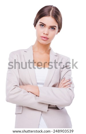 Beauty in business. Confident young businesswoman keeping arms crossed while standing against white background - stock photo