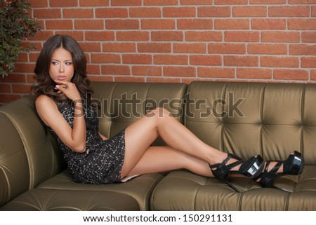 Beauty in formal dress. Beautiful young brown hair woman in formal dress lying on the couch and holding her hand on chin - stock photo