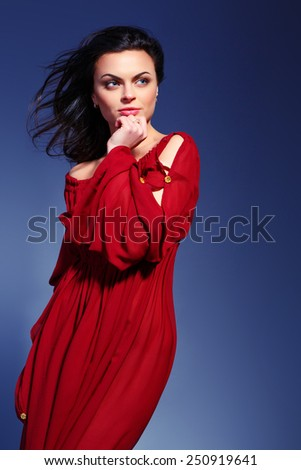 Beauty in marsala dress. Closeup fashion image of beautiful young woman in trendy marsala dress standing on dark blue background - stock photo