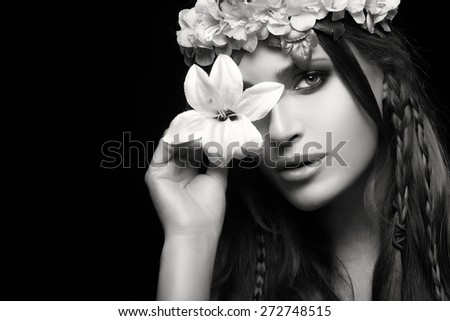 Beauty in spring concept. Gorgeous brunette woman holding a spring lily over one eye wearing a crown of flowers hairstyle. Beauty monochrome portrait isolated on black with copy space for text - stock photo