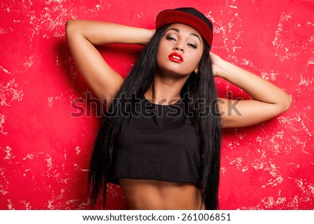Beauty in style. Attractive young African woman in baseball cap posing against red background