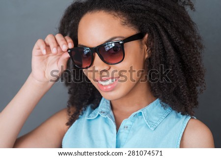 Beauty in style. Portrait of attractive young African woman adjusting her sunglasses and looking at camera with smile while standing against grey background