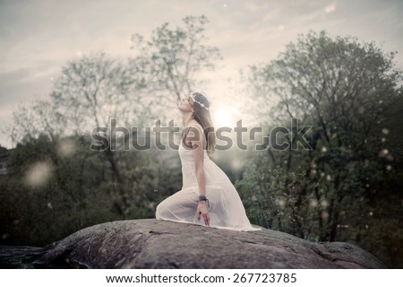 Beauty in white dress on her knees looking into the sky praying - stock photo