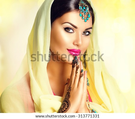 Beauty Indian girl with mehndi tattoos hold palms together. Beautiful Hindu exotic woman in sari and emerald oriental jewels looking in camera. India. Traditions concept - stock photo