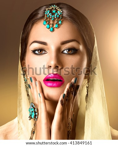 Beauty Indian woman portrait. Brunette Hindu model girl with brown eyes, mehndi or mehendi tattoo on her hand and national Indian jewels looking in camera. Indian girl in sari.  - stock photo