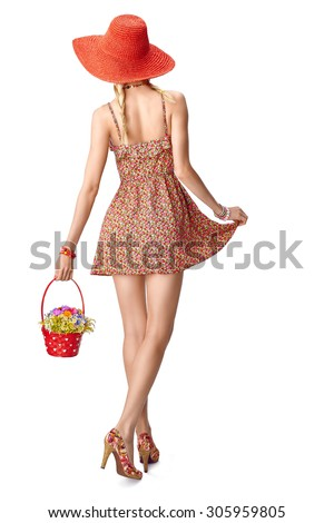 Beauty Joyful boho woman in hat, romantic style, people, back view. Young blonde pretty girl with red basket of wildflowers in floral sundress isolated on white. Playful lady, summer look - stock photo
