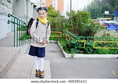 Beauty kid girl in uniform and jacket with backpack  on her way to school - stock photo