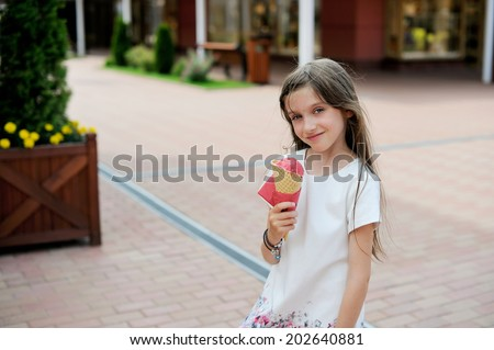 Beauty kid girl in white dress eating strawberry ice cream outdoors on the summer city street - stock photo