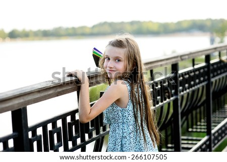 Beauty kid girl  on the bridge with paper boats in her hands