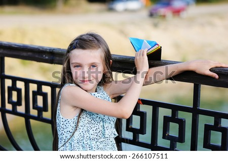Beauty kid girl  on the bridge with paper boats in her hands - stock photo