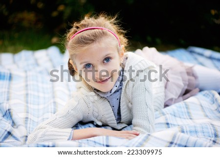Beauty kid girl with big blue eyes wearing white cardigan and skirt outdoor - stock photo