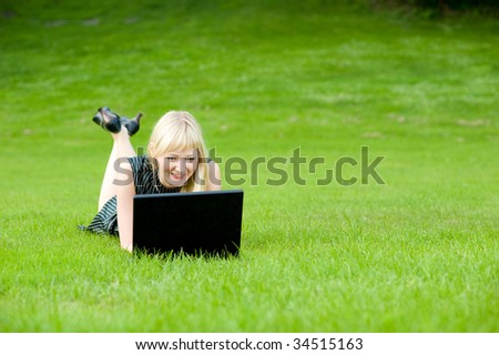 Beauty lady using a notebook computer in a park, shallow DOF and lots of copyspace - stock photo