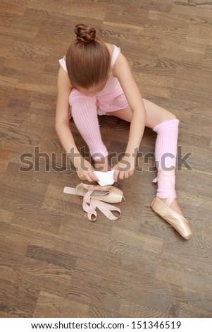 Beauty little ballerina in pointes on wooden background - stock photo