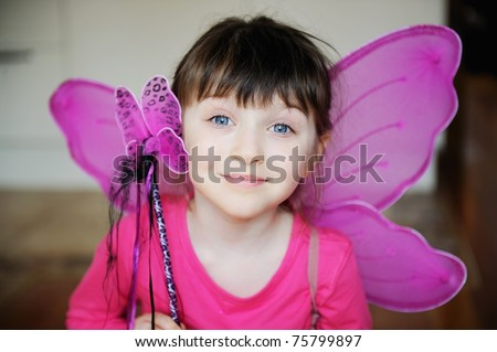 Beauty little girl with dark hair and blue eyes in pink shirt ans pink fairy wings with magic wand looks into the camera - stock photo