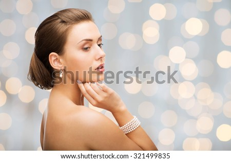 beauty, luxury, people, holidays and jewelry concept - beautiful woman with pearl earrings and bracelet over lights background