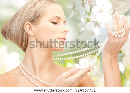 beauty, luxury, people, holidays and jewelry concept - beautiful woman with sea pearl necklace or beads over cherry blossom background - stock photo