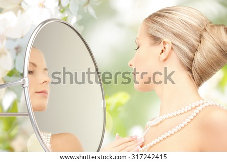 beauty, luxury, people, holidays and jewelry concept - beautiful woman with sea pearls beads or necklace looking to mirror over cherry blossom background - stock photo