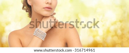 beauty, luxury, people, holidays and jewelry concept - close up of beautiful woman with pearl earrings and bracelet over yellow lights background - stock photo