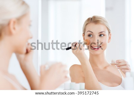 beauty, make up, cosmetics, morning and people concept - smiling young woman makeup brush and powder foundation looking to mirror at home bathroom - stock photo