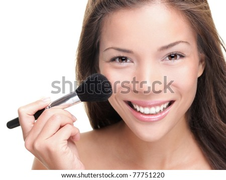Beauty makeup asian woman smiling closeup. Beautiful young woman applying foundation powder or blush with makeup brush. Isolated on white background. Mixed race Asian / Caucasian model. - stock photo