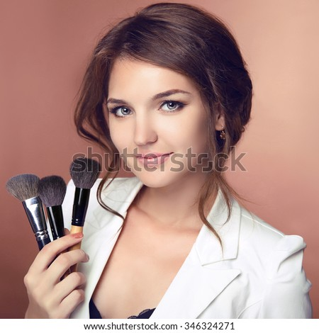Beauty makeup professional stylist. Makeup artist holding brushes. Attractive Woman face Portrait.  Isolated on studio background. - stock photo