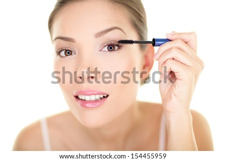 Beauty makeup woman putting mascara eye make up on eyes. Asian fresh face girl looking in the mirror looking at camera isolated on white background. Mixed race ethnic Asian Chinese / Caucasian model. - stock photo