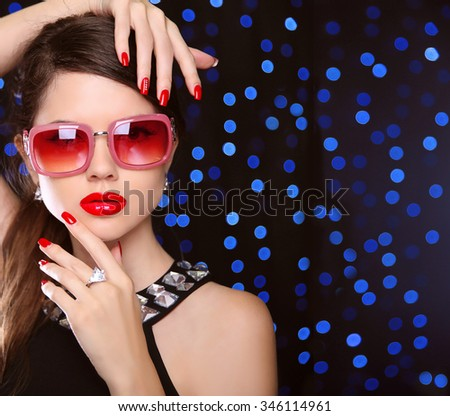 Beauty. manicured nails. Fashion model girl in sunglasses with bright makeup, luxurious jewelry over  on blue lights background. - stock photo