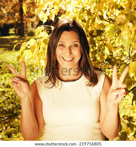 beauty mature brunette woman in park smiling close up