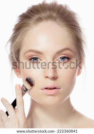 Beauty model applying foundation on her face - stock photo