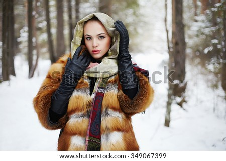 Beauty model girl in winter forest. beautiful young Woman in fashionable Fur Coat and scarf. siberian luxury stylish blond girl snow around - stock photo