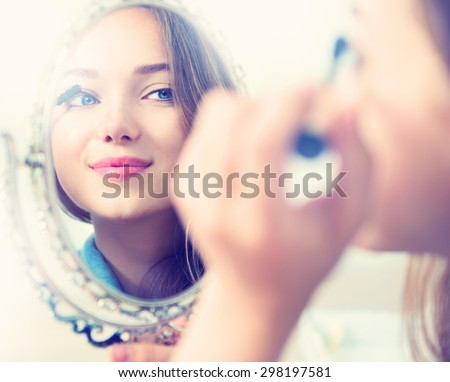 Beauty model girl looking in the mirror and applying mascara make up. Beautiful young woman apply makeup - stock photo