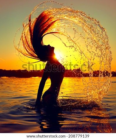 Beauty Model Girl Splashing Water with her Hair. Teen girl Swimming and splashing on summer beach over sunset. Beautiful Woman in Water  - stock photo