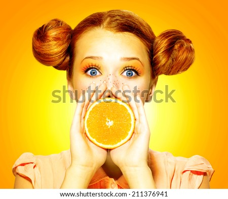 Beauty Model Girl takes Juicy Oranges. Beautiful Joyful teen girl with freckles, funny red hairstyle and yellow makeup . Professional make up. Orange Slices  - stock photo