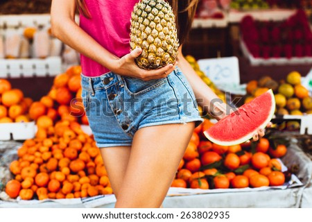 Beauty Model Girl takes Juicy Watermelon and  Pineapple.Beautiful Joyful teen girl with freckles.Having fun on fruit market.Watermelon Slices.Summer colors,trendy teenage summer hipster,tropical fruit - stock photo