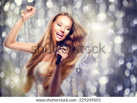 Beauty model girl with a microphone singing and dancing over holiday glowing background. Karaoke party singer. Disco party. Celebration - stock photo