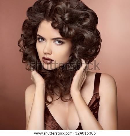 Beauty Model girl with Healthy Brown Hair. Beautiful brunette woman touching her curly smooth shiny hair. Wavy Hairstyle. Hair cosmetics, haircare.