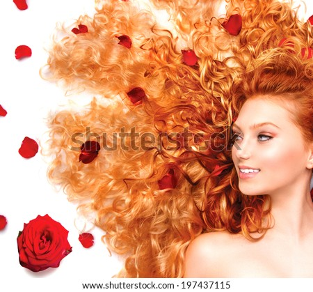 Beauty model girl with healthy long curly red hair and beautiful hairstyle decorated with red roses petals. Fashion woman with Wavy healthy hair isolated on white background. - stock photo